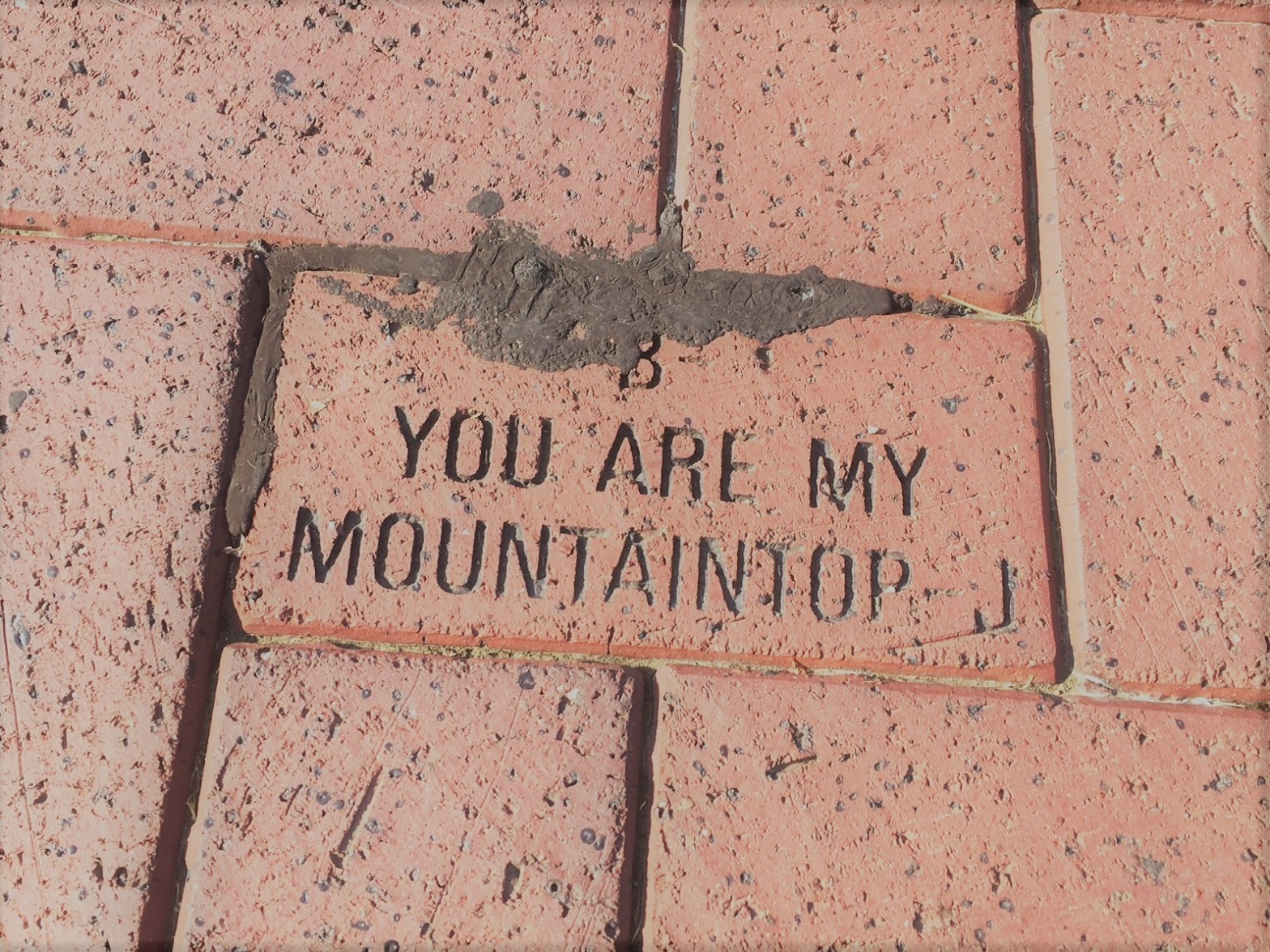 A brick with the words 'You are my mountaintop' engraved