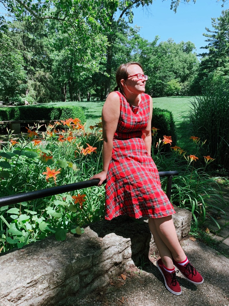 picture of the writer leaning against a railing outside in a red plaid dress. orange tiger lilies are behind the rail