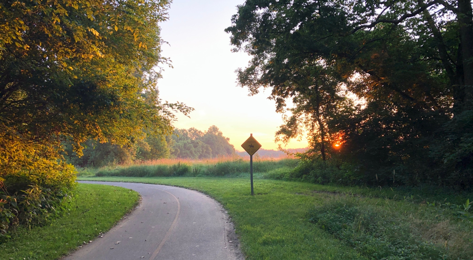 A running path curving to the left out of sight as the sun crests the horizon.