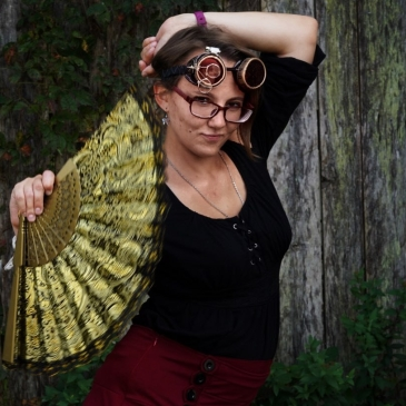 Woman wearing steampunk goggles and holding a golden fan extended.