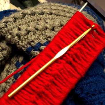A golden crochet hook attached to red yarn and a hairpin lace crochet apparatus