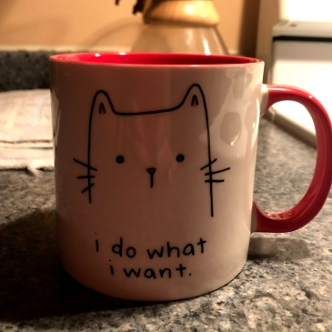 "A cup with a cat face that says ""i do what i want"""