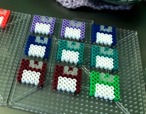 Brightly colored perler bead crafts arranged in the shape of floppy disks.
